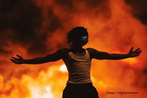 copyright Adja Gildersleve: A black man in a white tank top stands with his arms stretched out wide. He stands in front of  a sky filled with flames.