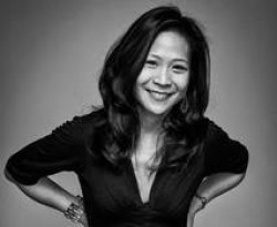 A black and white photo of director May Adrales. She is smiling.