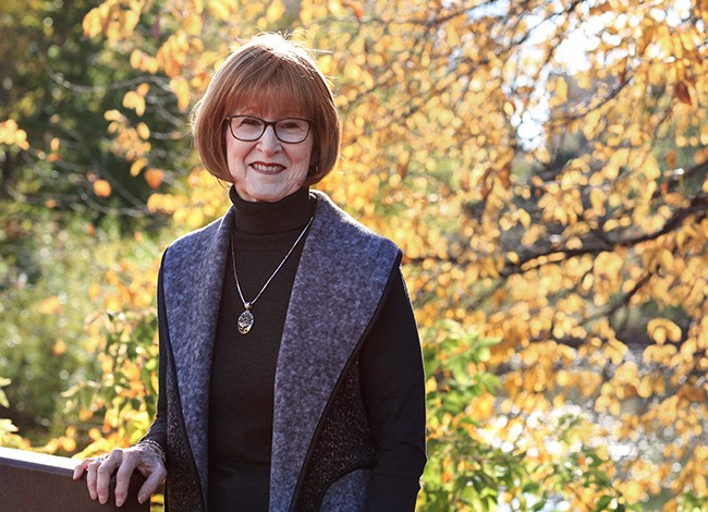 Ginger Wilhelmi smiles at the camera. She is wearing glasses, a black turtleneck, and pendant necklace. The background of fall foliage, with yellow, red, and green leaves compliments her auburn hair.